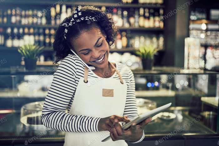 Junger afrikanischer Unternehmer beschäftigt Reservierungen in ihrem Café