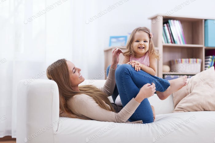 Cute little girl have fun with mother on sofa