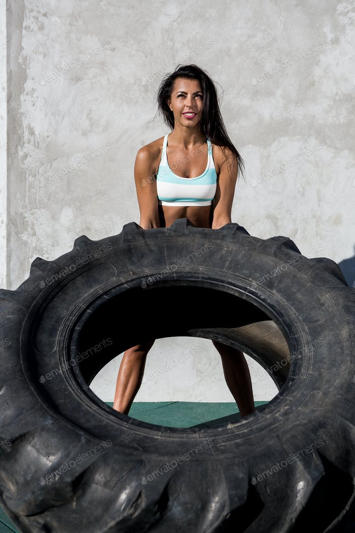 Sporty girl exercise with big tire.