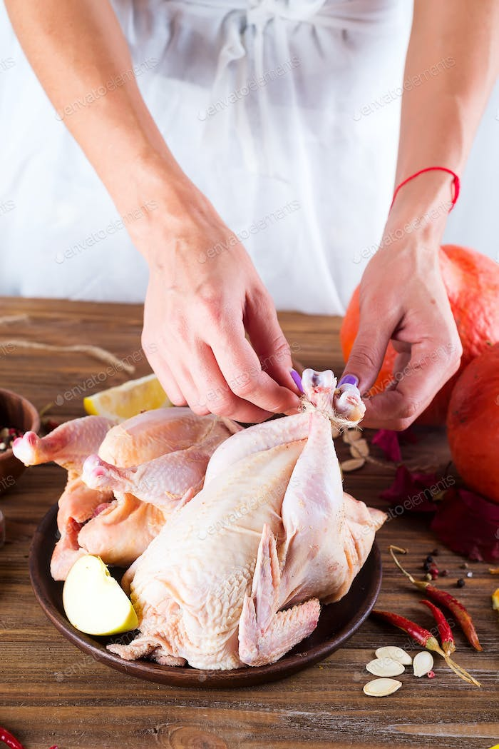 Raw whole chicken in a plate on a wooden table. The woman's hands prepare the chicken for frying.