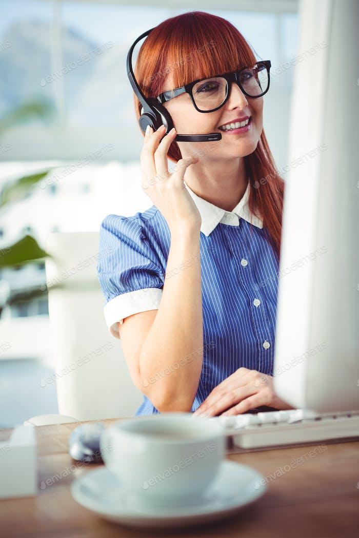 Attractive hipster woman with headset in her office