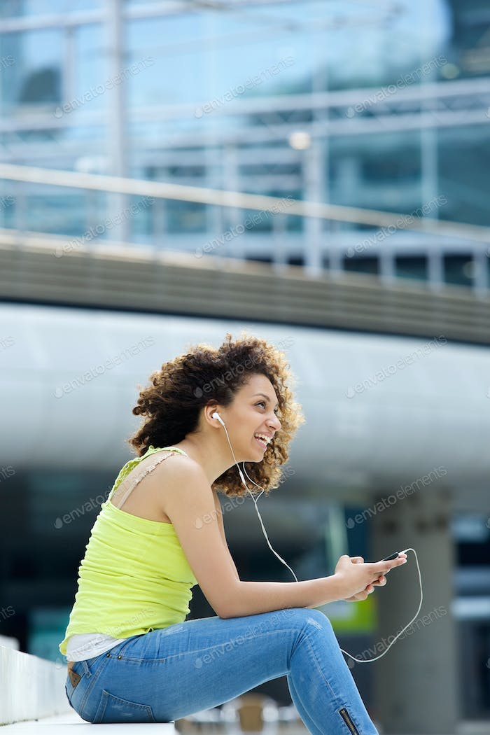Woman smiling with earphones outside