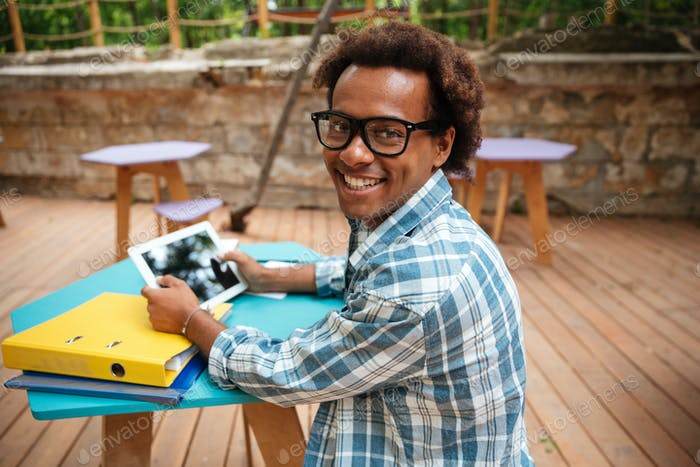 Cheerful african young man using tablet in outdoor cafe