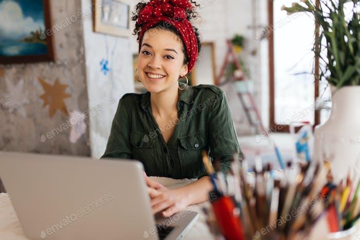 Молодая привлекательная женщина с темными вьющимися волосами сидит за столом