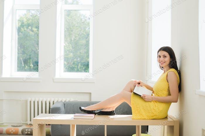Studentin Vorbereitung auf die Prüfung. Teenager Mädchen studieren sitzen auf einem rack zu Hause im Wohnzimmer