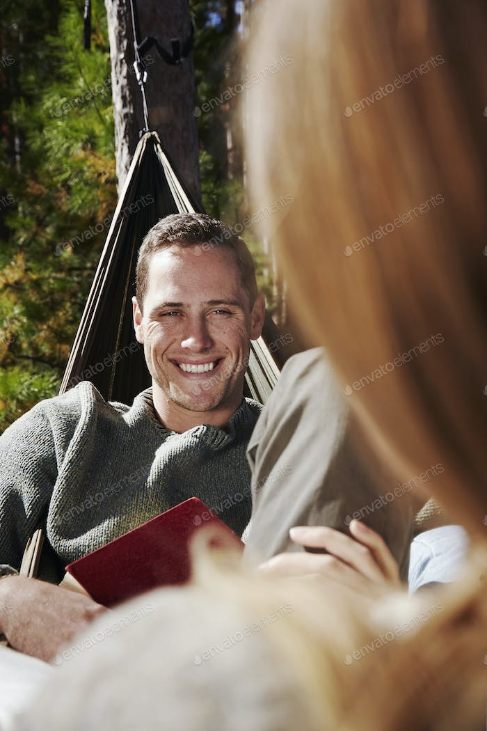 Two people sitting in hammocks outdoors. A man smiling at a companion.
