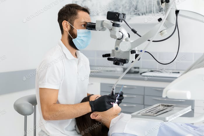 Professional dentist using modern technologies in treatment