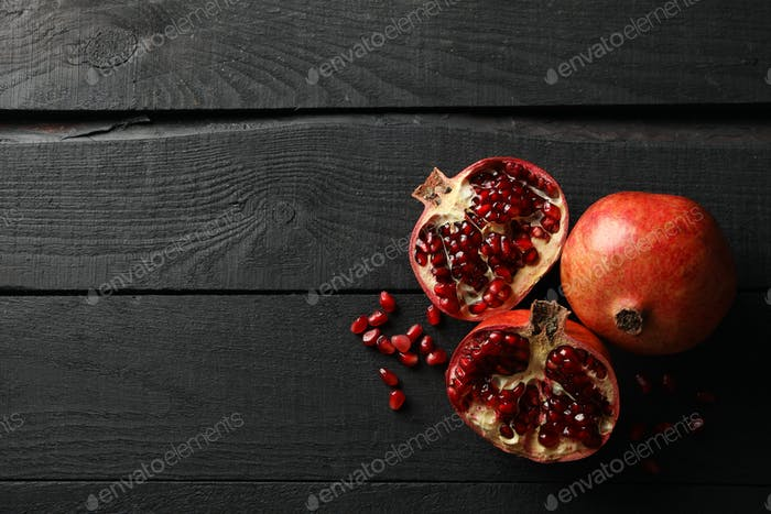 Pomegranate on wooden background, top view. Juicy fruit