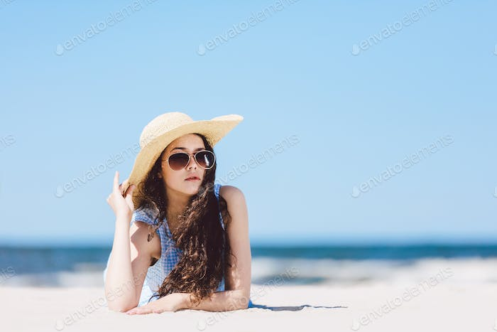 Pretty girl laying on the beach, wearing hat and sunglasses.
