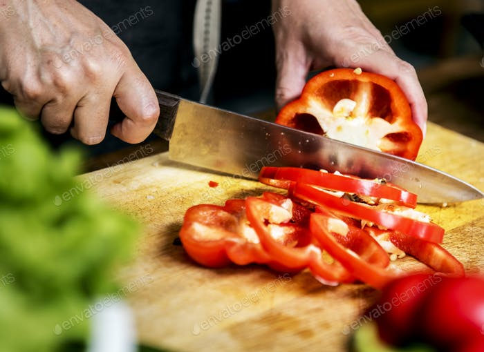 Closeup of hand with knife cutting bell pepper