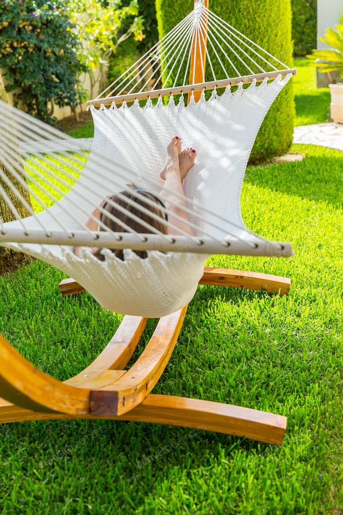 Girl relaxing and listening to music in hammock
