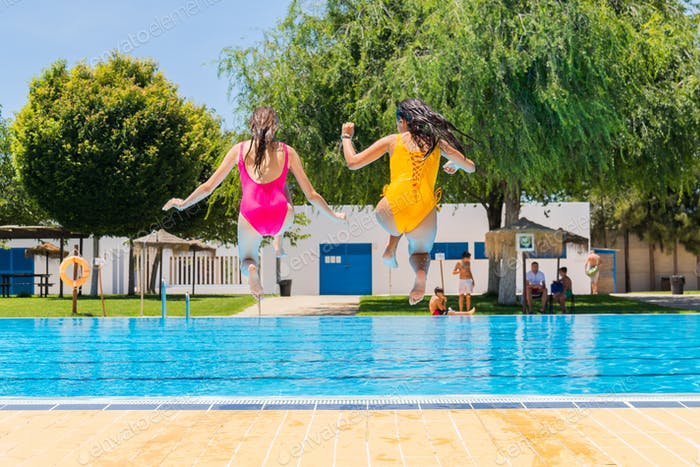 Two teenage girls jumping in a swimming pool. Two girls jumping into a swimming pool