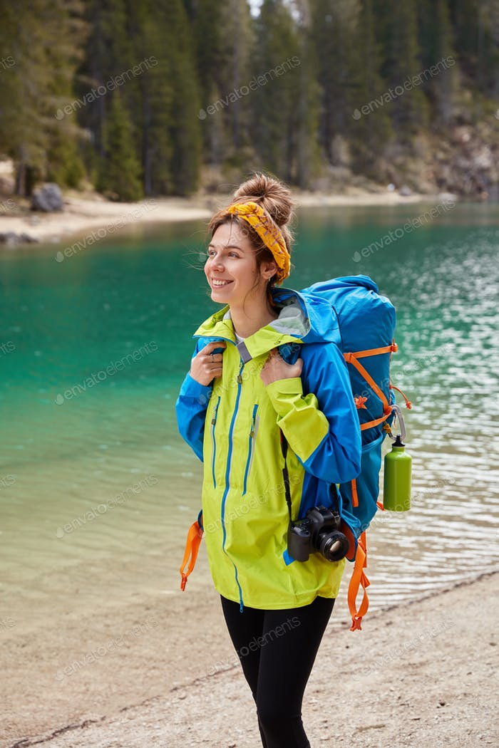 Vertical shot of tourist girl walks by turquoise lake, coniferous forest, smiles joyfully holds came