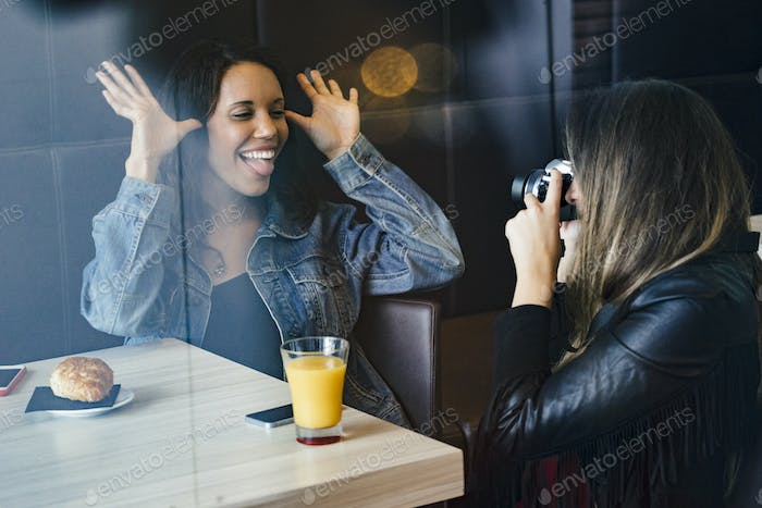 two female caucasian and african american friends having a coffee and taking picture