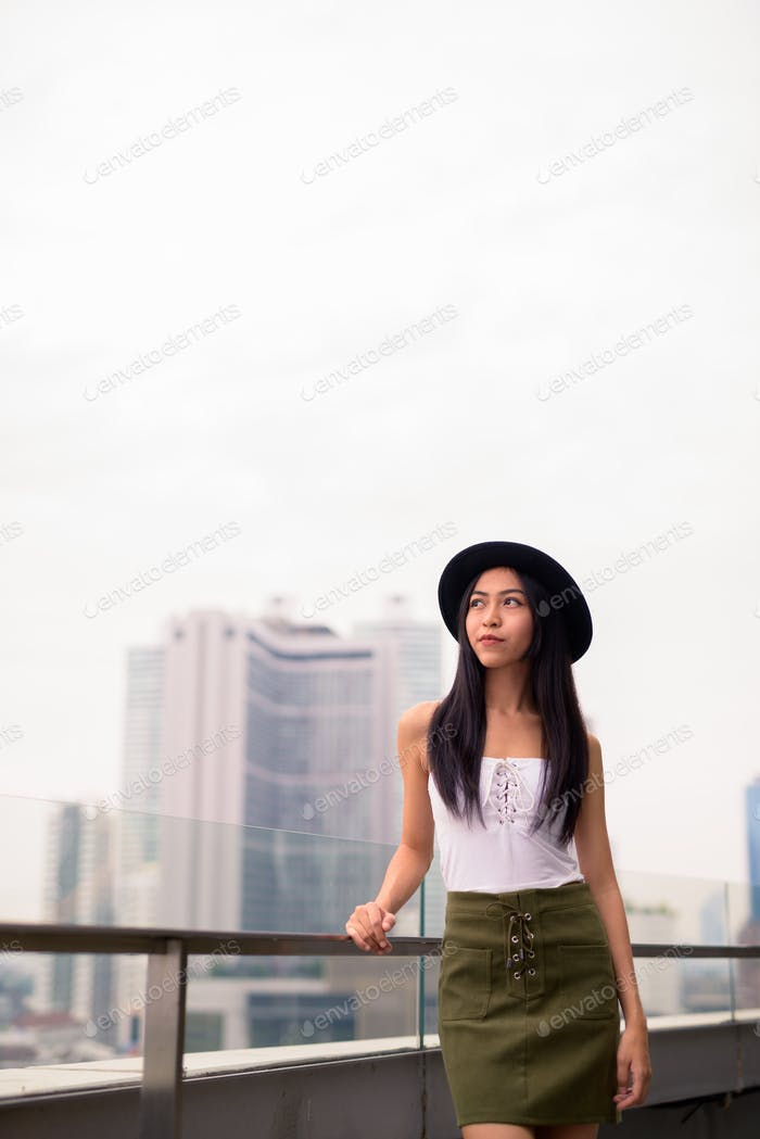 Young beautiful Asian tourist woman thinking against view of the city