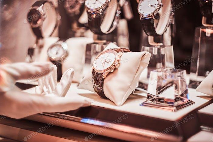 Nahaufnahme der Hand in Handschuhen des Verkäufers zeigt die exklusive Herrenuhr aus der neuen Sammlung