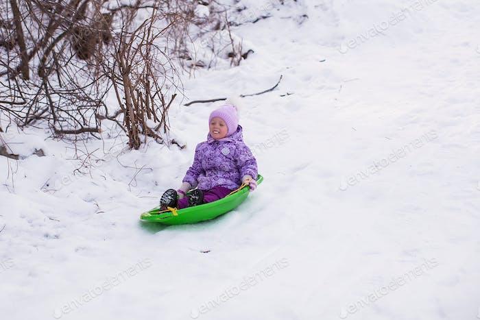 Adorable little girl sledding in snowy forest