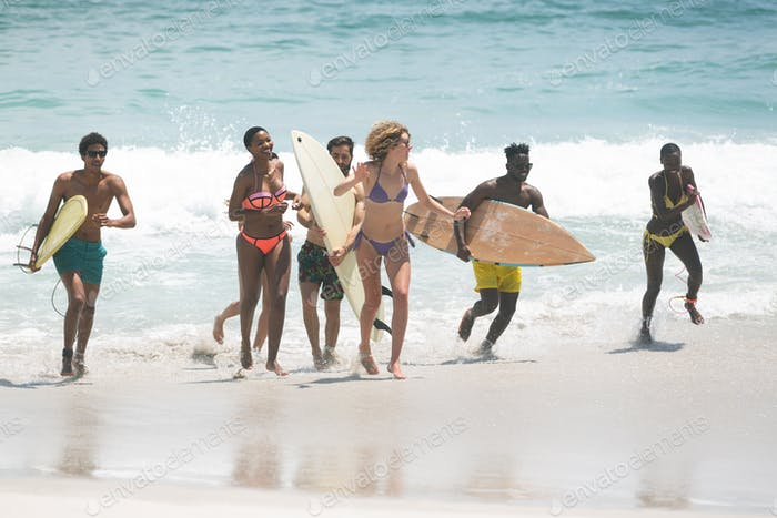 Group of multi ethnic friends holding surfboard and running at beach on a sunny day while running