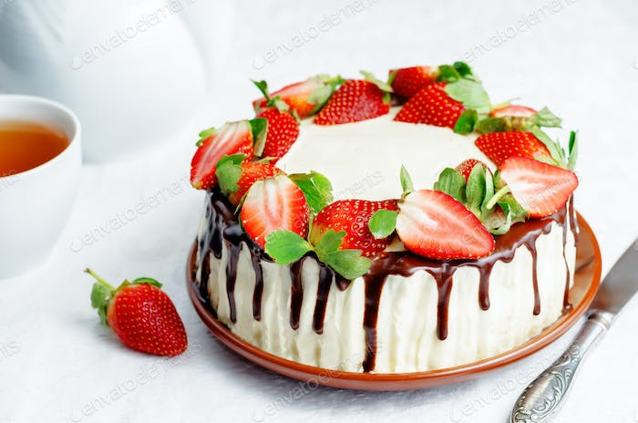 Sponge cake with cream, chocolate and strawberry