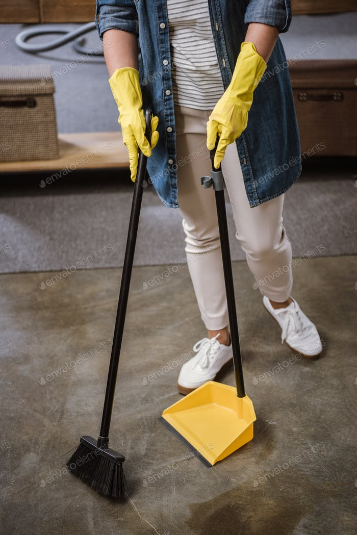 Partial view of woman in gloves sweeping floor with broom and dustpan