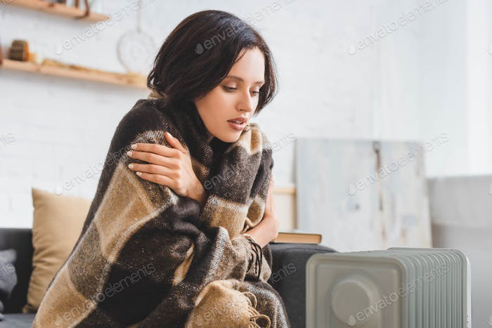 beautiful girl with blanket warming up with heater in cold room