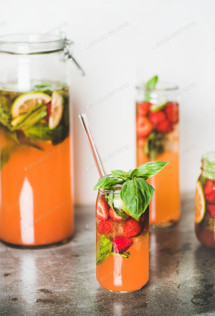 Fresh homemade lemonade or iced-tea with strawberry and basil leaves