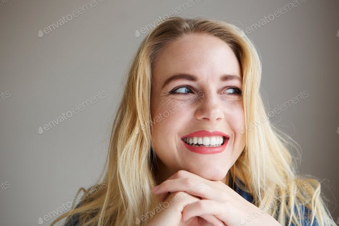 happy young blond woman leaning on hand and laughing