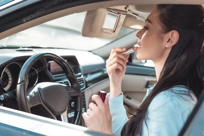 Young attractive woman applying lipstick in car, using a sun visor mirror