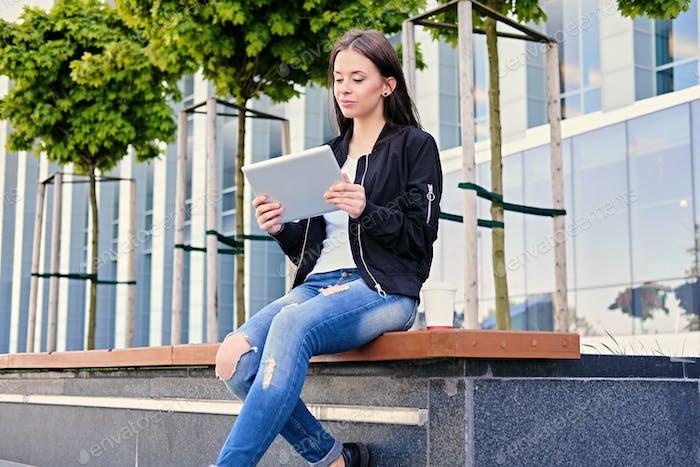 Brünette weibliche Studentin mit Tablet-PC auf einer Stadtstraße.