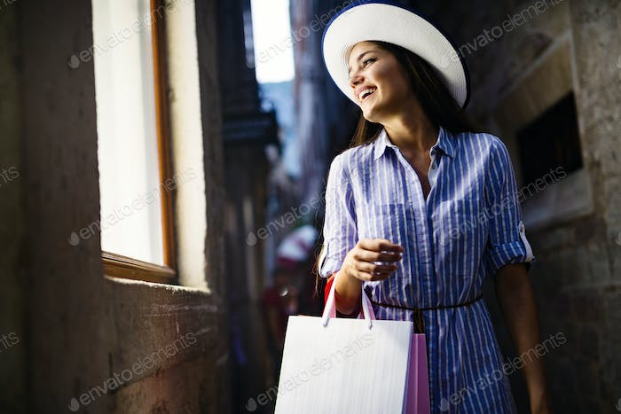 Consumerism, shopping, lifestyle concept. Happy woman with bags enjoying shopping