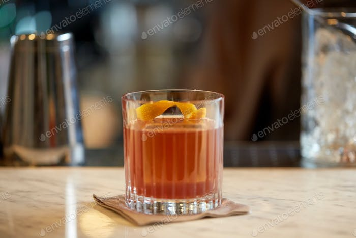 glass of cocktail with orange peel at bar
