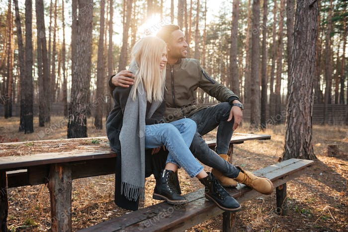 Cheerful loving couple sitting outdoors in the forest