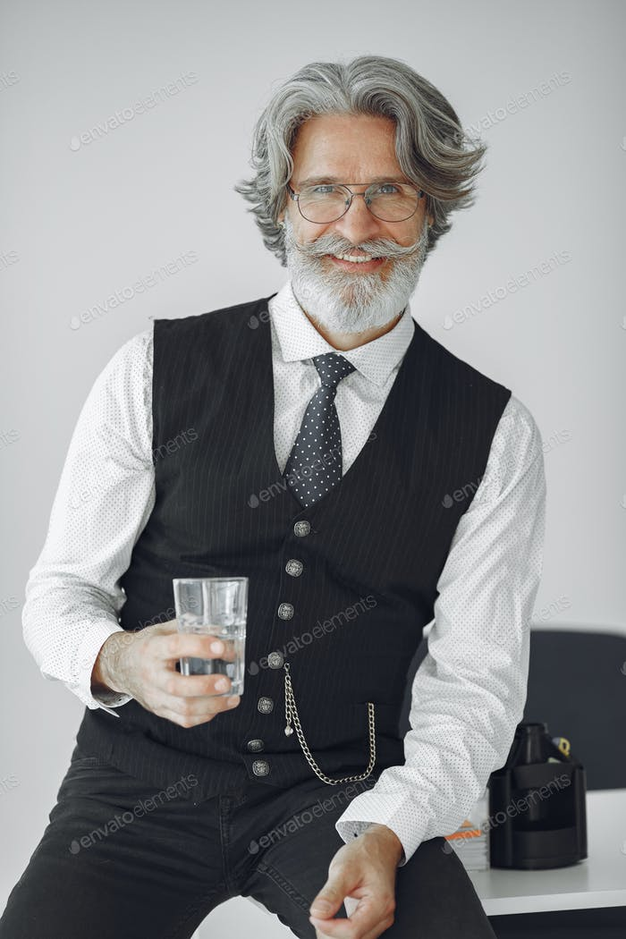 Handsome old businessman sitting with glass of water