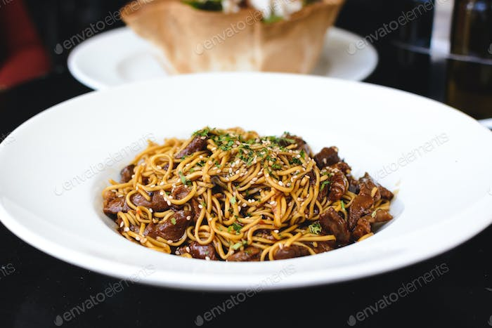 Fried egg noodles with sesame, beef and oyster sauce