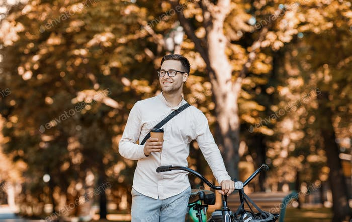 Modern lifestyle and ecological transport. Happy hipster holding coffee and walking with bike