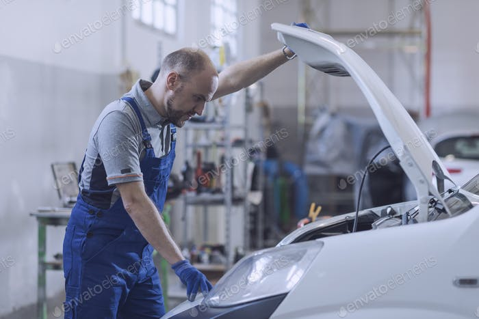 Professional mechanic checking the car engine