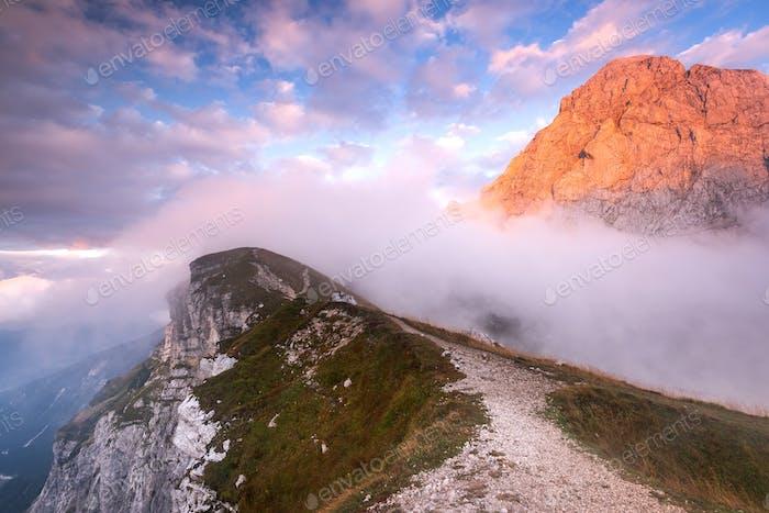 Mangart Mountains Peak above Clouds at Dramatic Sunset in Julian