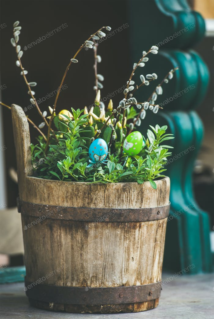 Green plants, colored eggs, willow tree branches in wooden tub