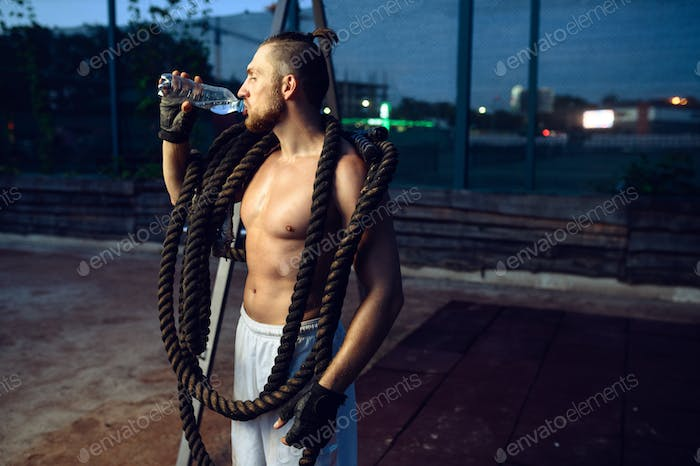 Muscular man with crossfit ropes drinks water