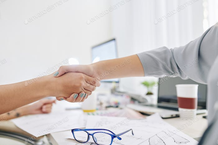 Creative managers shaking hands