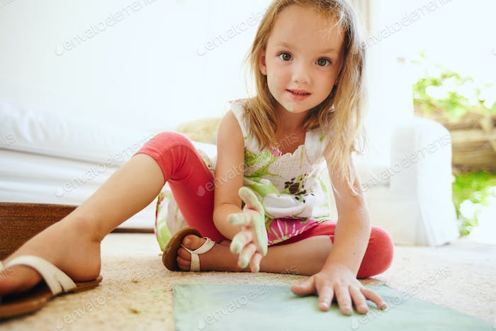 Cute girl drawing sitting on the floor