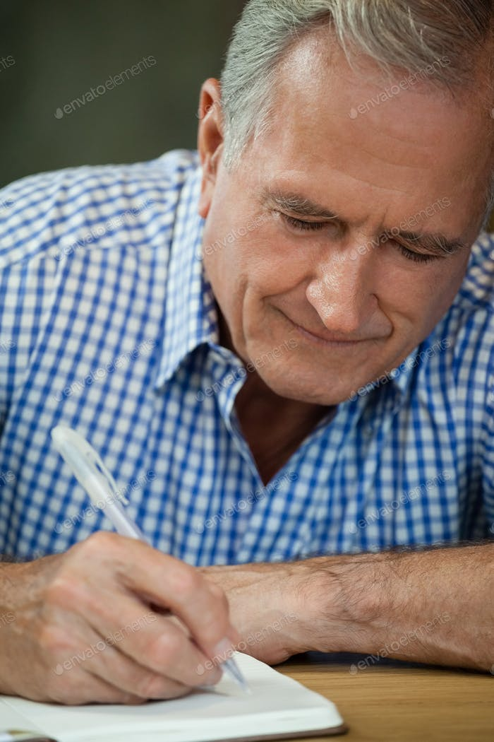 Close up of senior man writing on diary