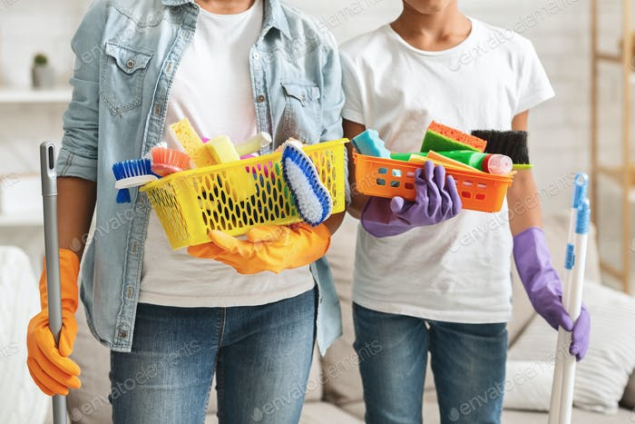 Cropped image of girls holding cleaning tools