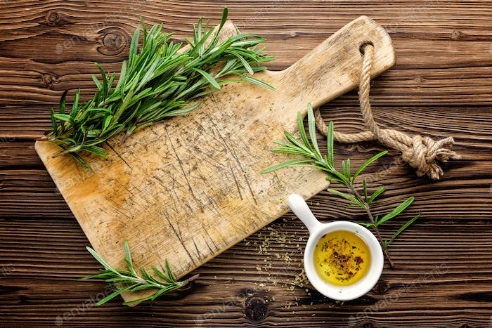 Culinary background with wooden board and cooking ingredients, olive oil and rosemary