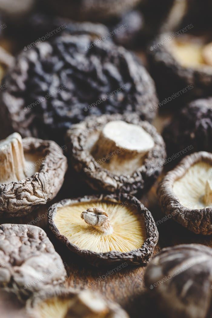Macro photography of Chinese dried mushrooms Shiitake on a wooden kitchen board.