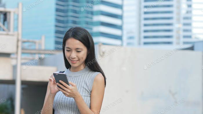 Woman sending sms on cellphone in city