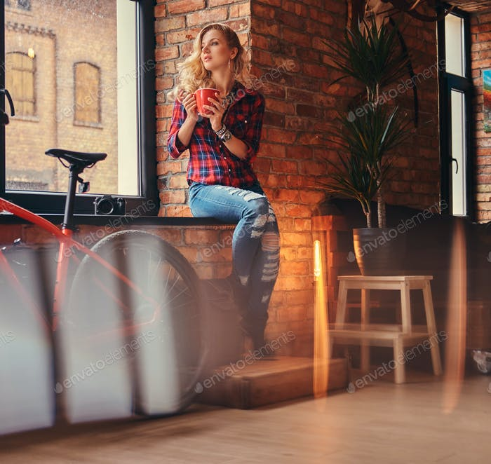 Sensual blonde hipster girl in a studio with loft interior.