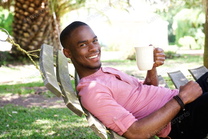 Young african man with a coffee relaxing on hammock