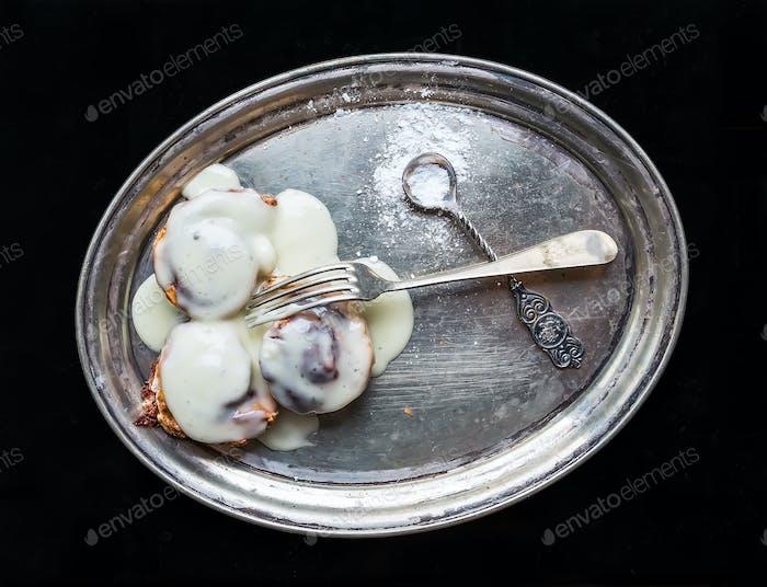 Zimtrollen mit Sahneglasur und Zuckerpulver auf einer Metallschale