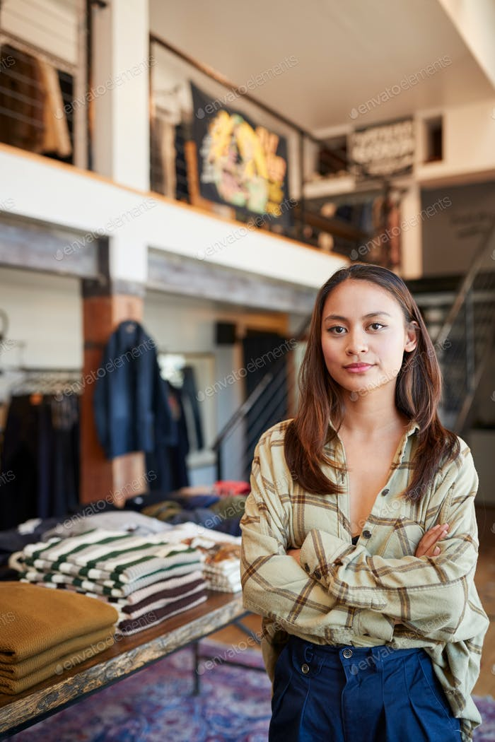 Portrait Of Female Owner Of Fashion Store Standing In Front Of Clothing Display